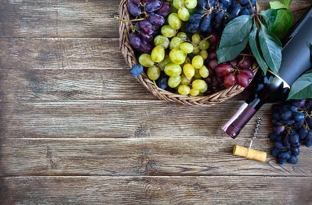 Fles met rode wijn, kurkentrekker, blauwe druiven in mand, bladeren op een houten tafel.