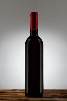 Fles met rode wijn met een licht verloop op de achtergrond