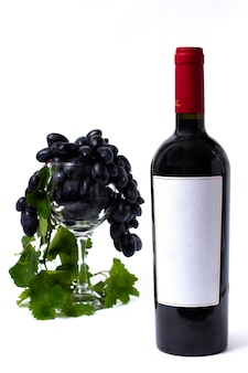 Fles met rode wijn, wijnglas met druiven, op een witte achtergrond, geen mensen, verticaal