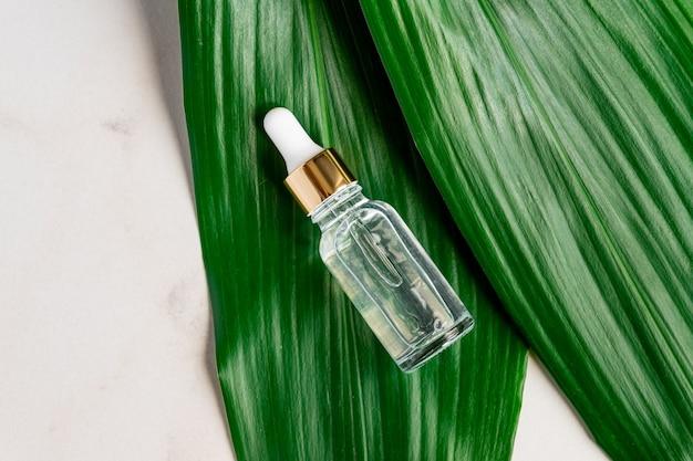 Fles met serum op marmeren tafel, groen palmblad op het oppervlak