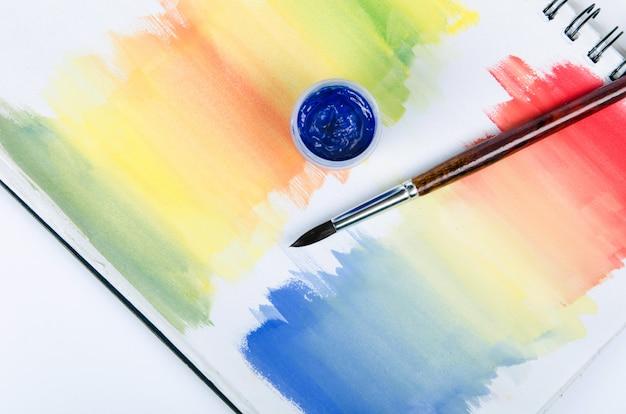Fles met verf en penseel met gekleurde notitieblok