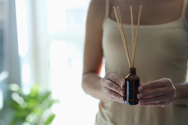 Fles met wierookstokjes in vrouwelijke handen. oosterse geneeskunde en ontspanningsconcept