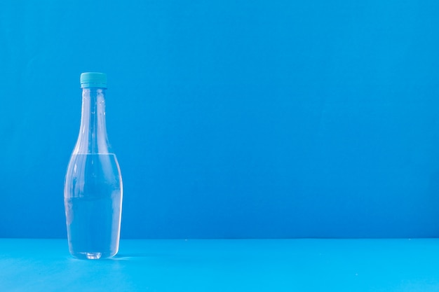 Fles mineraalwater op blauwe achtergrond.