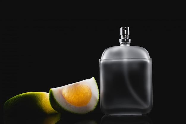 Fles moderne mannelijke parfum en citrus plakjes op donkere achtergrond