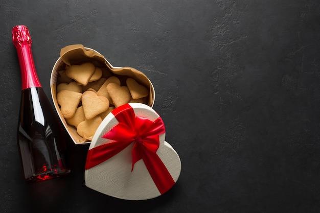 Fles mousserende wijn, koekjes en cadeau als hart op zwarte achtergrond. valentijnsdag wenskaart. uitzicht van boven. ruimte voor tekst.