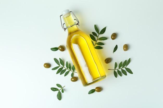 Fles olie, olijven en twijgen op wit oppervlak