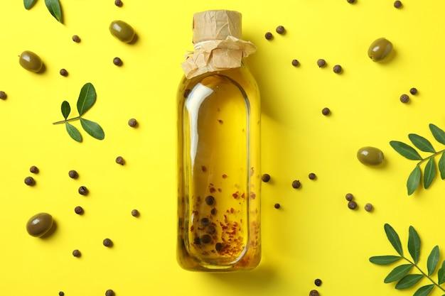 Fles olijfolie en kruiden op gele achtergrond
