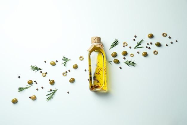 Fles olijfolie, olijven en kruiden op witte ondergrond
