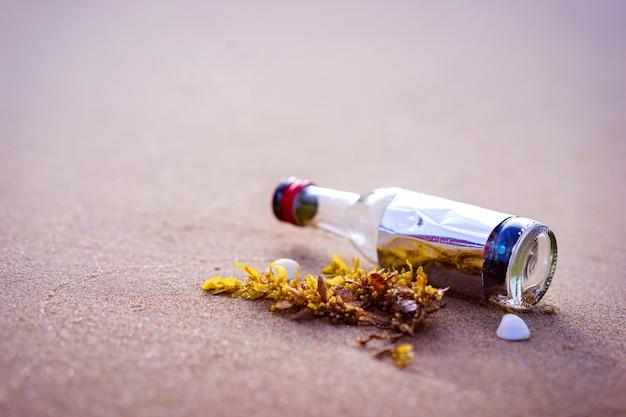 Fles op een zandstrand in de ochtend