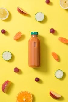 Fles oranje fruit en groentesap in het midden van de afbeelding, omringd door stukjes fruit en groenten van verschillende kleuren op een gele achtergrond