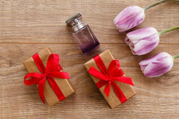 Fles parfum en geschenkdozen op houten planken met lila tulpen.