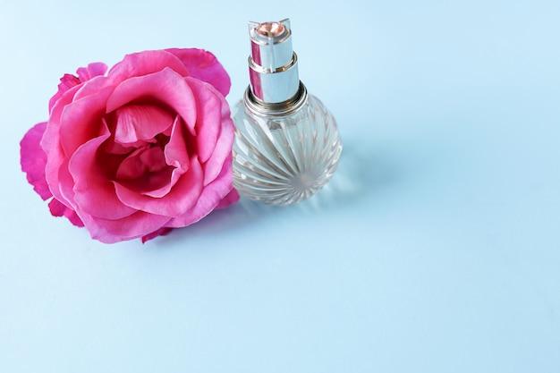 Fles parfum met bloem roos op blauw, kopie ruimte
