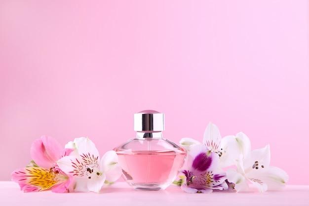Fles parfum met bloemen op roze