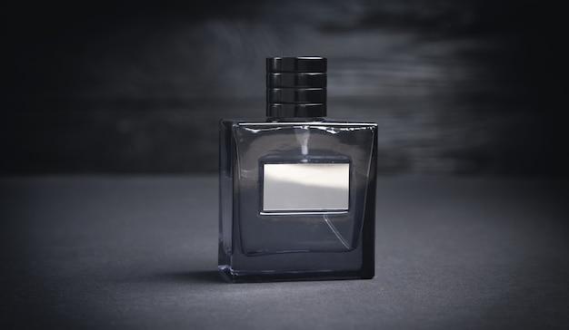 Fles parfum op de zwarte achtergrond.