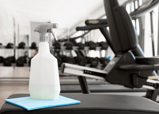 Fles reinigingsoplossing op sportschoolbank