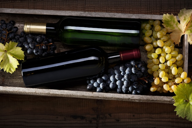 Fles rode wijn en een fles witte wijn, zwarte druiven en witte druiven met druivenbladeren op een oude houten tafel.
