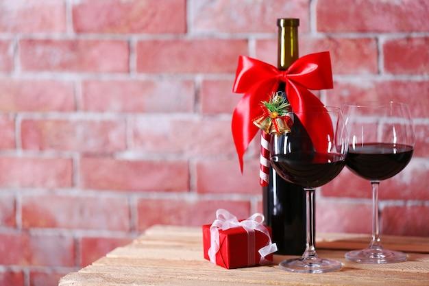 Fles rode wijn en glazen met kerstcadeaus op muuroppervlak