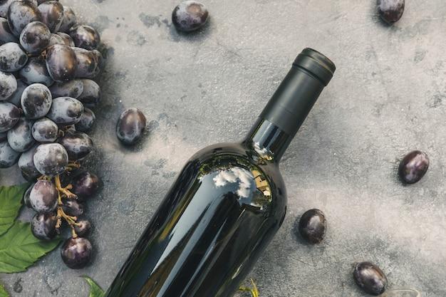 Fles rode wijn en rijpe druif op vintage donkere stenen tafel achtergrond bovenaanzicht kopie ruimte voor tekst...