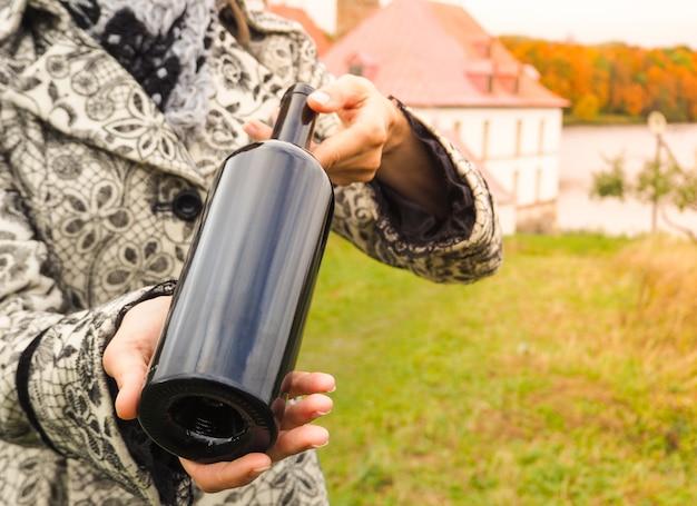 Fles rode wijn in vrouwelijke handen