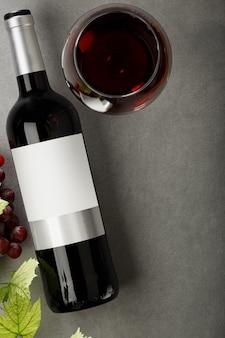 Fles rode wijn met etiket. glas wijn en druif. mockup voor wijnflessen. bovenaanzicht.