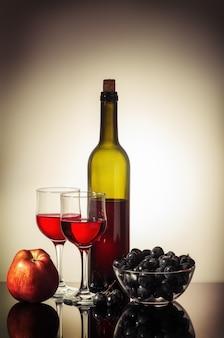 Fles rode wijn twee glazen een appel en een beker met druiven op een tafel