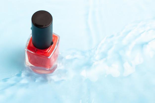 Fles rood gekleurd nagellak op blauwe waterachtergrond met golf en exemplaarruimte. bovenaanzicht.