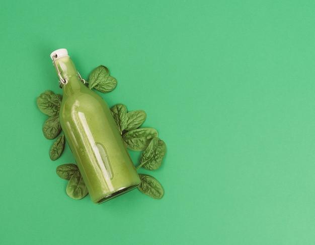Fles spinaziesap met spinazieblaadjes op een groene achtergrond. kopieer ruimte.