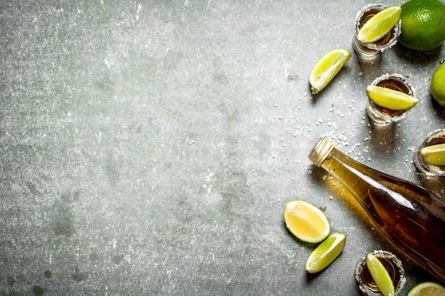 Fles tequila met limoen en zout op stenen tafel.