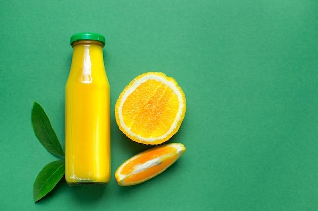 Fles vers sinaasappelsap appelsap plat leggen kopie ruimte geïsoleerd op groen bovenaanzicht