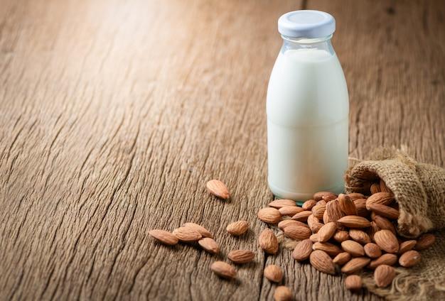 Fles verse melk en amandelen op houten tafel