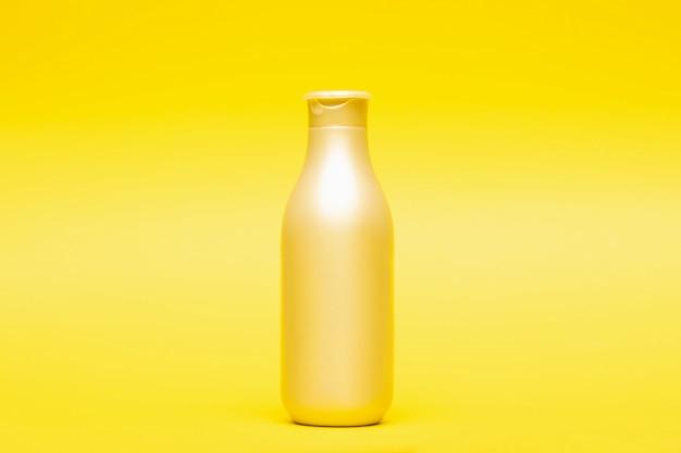 Fles voor haarshampoo en veredelingsmiddel op gele muur