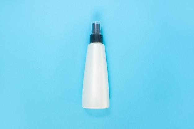 Fles voor vloeistof, crème, gel, lotion. kosmetische fles op blauw. plat leggen