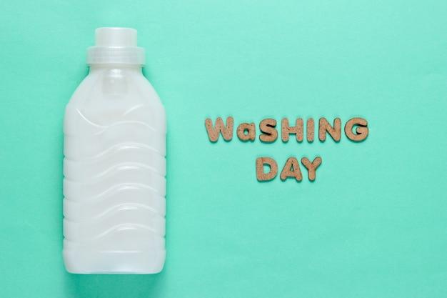Fles wasgel op blauwe oppervlakte met de tekst wasdag
