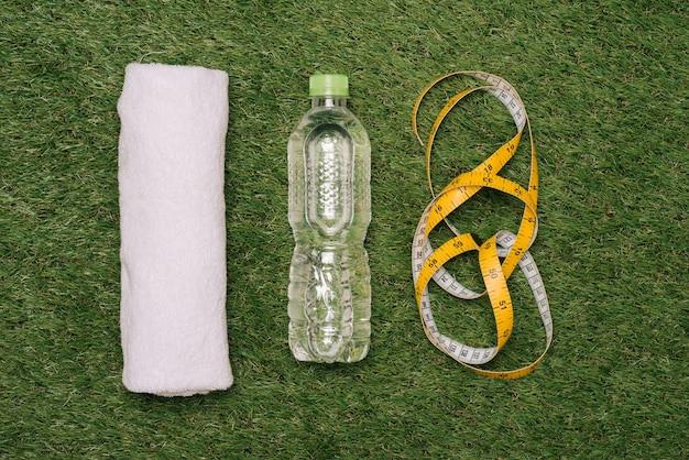 Fles water en springtouw op groen gras achtergrond. bovenaanzicht. fitness, sport en gezonde levensstijl concept.