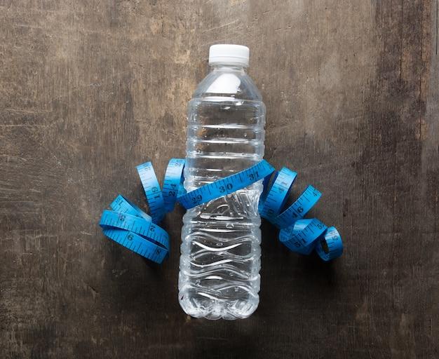 Fles water met een meetlint