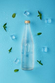 Fles water met ijsblokjes en muntblaadjes