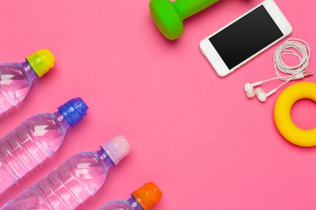 Fles water, mobiele telefoon met koptelefoon op roze achtergrond