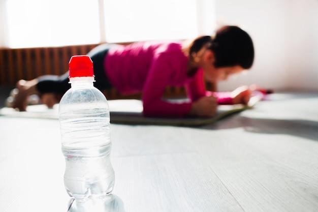 Fles water op de voorgrond. klein meisje doet een plank exercise-training thuis. schattige jongen traint binnen op een mat. klein donkerharig vrouwelijk model heeft oefeningen bij het raam in haar kamer.