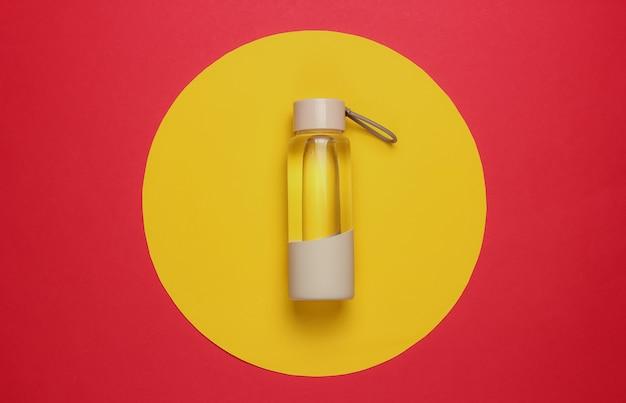 Fles water voor sport en buitenactiviteiten op de achtergrond van de rode gele cirkel. bovenaanzicht