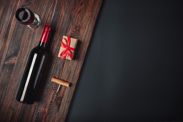 Fles wijn cadeau vak kurkentrekker en wijnglas op roestig