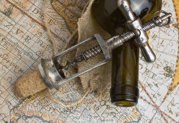Fles wijn en een kurkentrekker op de achtergrond van oude kaarten