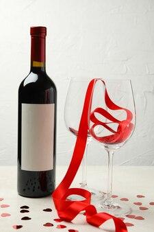 Fles wijn en glazen met glitter en lint op witte gestructureerde tafel