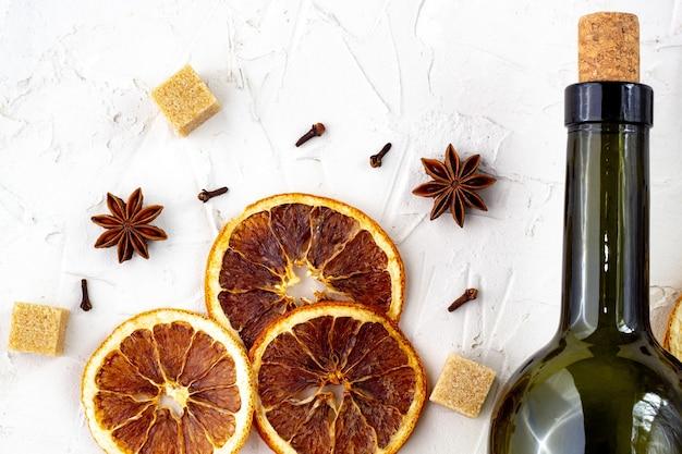 Fles wijn en kruiden op witte achtergrond. ingrediënten voor een glühwein. kaneel, anijssterren, sinaasappel, bruine suiker, kruidnagel. kerst warme drank