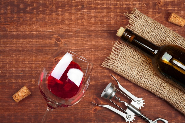 Fles wijn en kurk en kurketrekker op houten tafel