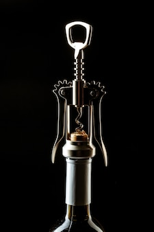 Fles wijn en kurketrekker in het donker