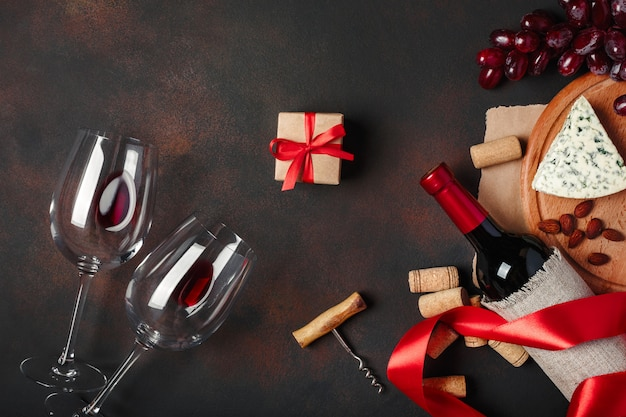 Fles wijn, geschenkdoos, blauwe stinkende kaas, rode druiven, amandelen, kurkentrekker en kurken, op roestige achtergrond