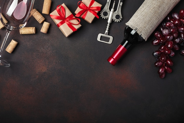 Fles wijn, geschenkdoos, rode druiven, kurkentrekker en kurken, op roestige achtergrond