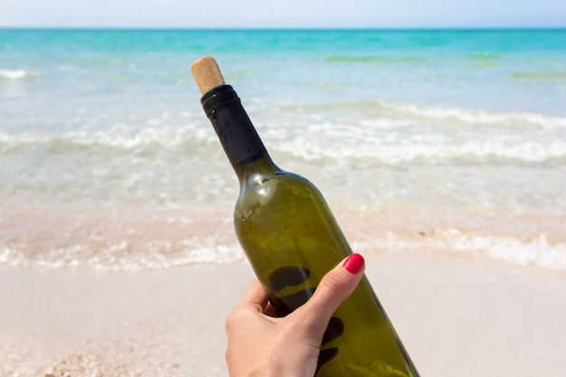 Fles wijn in zand op het strand
