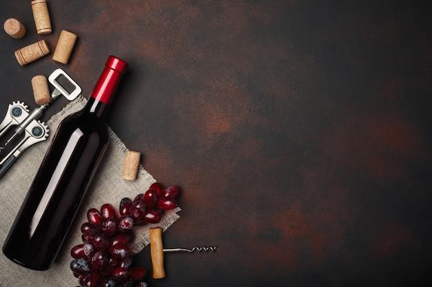 Fles wijn, kurkentrekker en kurken, op roestige achtergrond bovenaanzicht