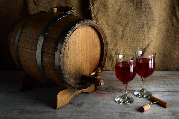 Fles wijn met een glas en een kurketrekker op een houten achtergrond